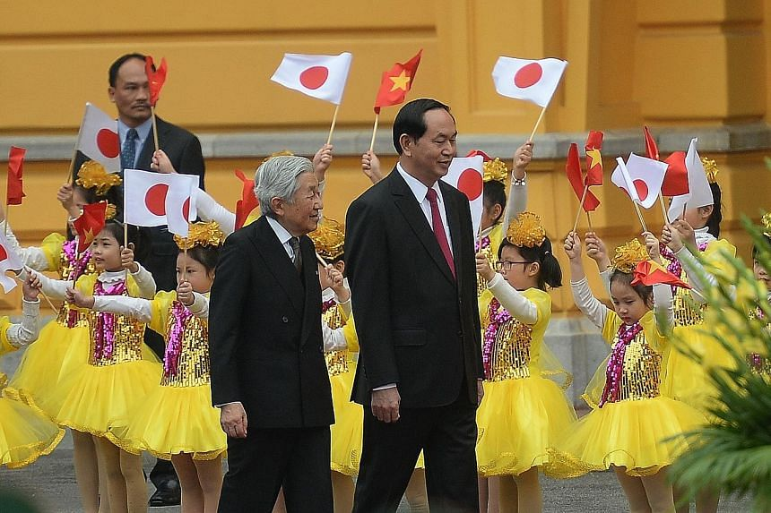 Children greeting Emperor Akihito (left) and Mr Quang at a welcoming ceremony at the presidential palace in Hanoi yesterday.