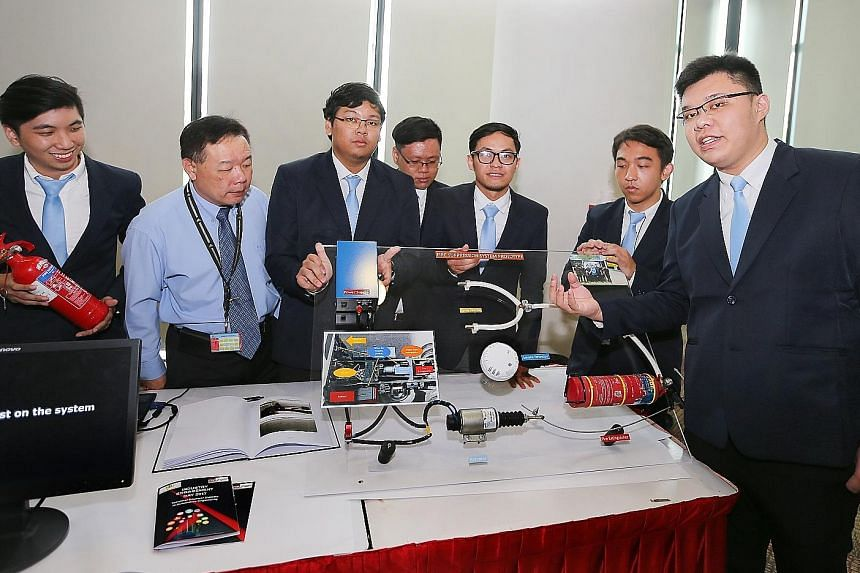 ITE lecturer Pang Tyng Fa (in blue), with his students (from left) Oscar Pong, Willy Tho, Dominic Yeo, Muhammad Irsyad Amin S., Stanley Ng and Tan Yi Ying, presenting the team's vehicle fire-suppression system yesterday. The automotive engineering st