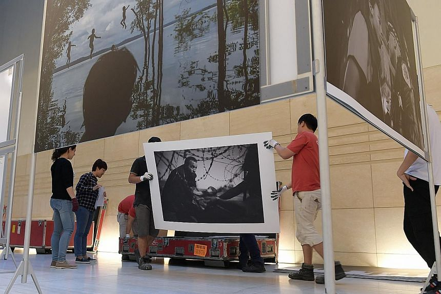 Workers preparing to mount the winning image of the World Press Photo 2016 competition, taken by Australian photojournalist Warren Richardson, during the setting up of the World Press Photo 2016 exhibition at official venue supporter, the National Mu