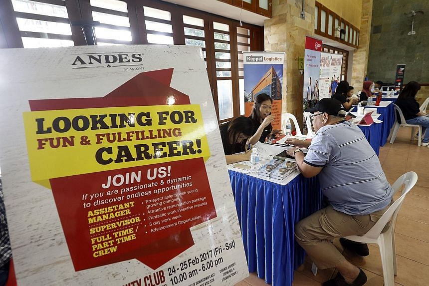 A job seeker being interviewed at a fair. To help workers pick up skills, NTUC will work with institutions to produce training modules relevant to employers.