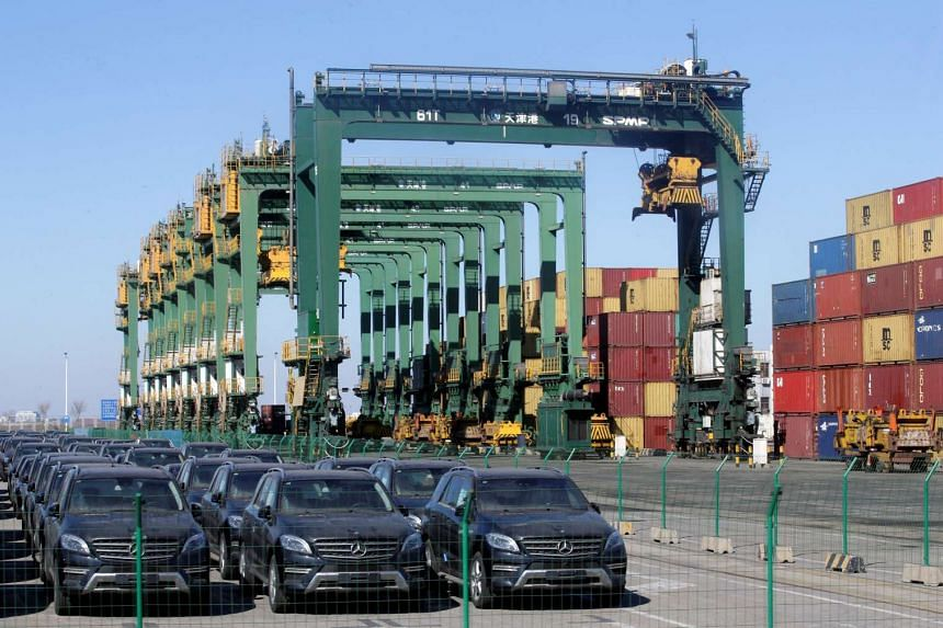 Imported Mercedes Benz cars sit near containers at Tianjin port on Feb 23, 2017.
