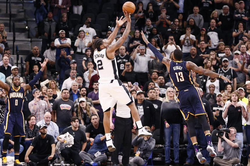 San Antonio Spurs forward Kawhi Leonard (#2) shooting the game-winner over Indiana Pacers forward Paul George (#13) during their NBA match on March 1, 2017.