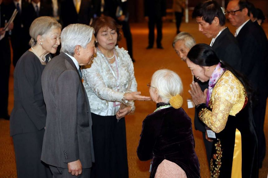 Japan's Emperor Akihito (second left) and Empress Michiko (left) meeting with the families of Japanese veterans living in Vietnam, in Hanoi on March 2, 2017.