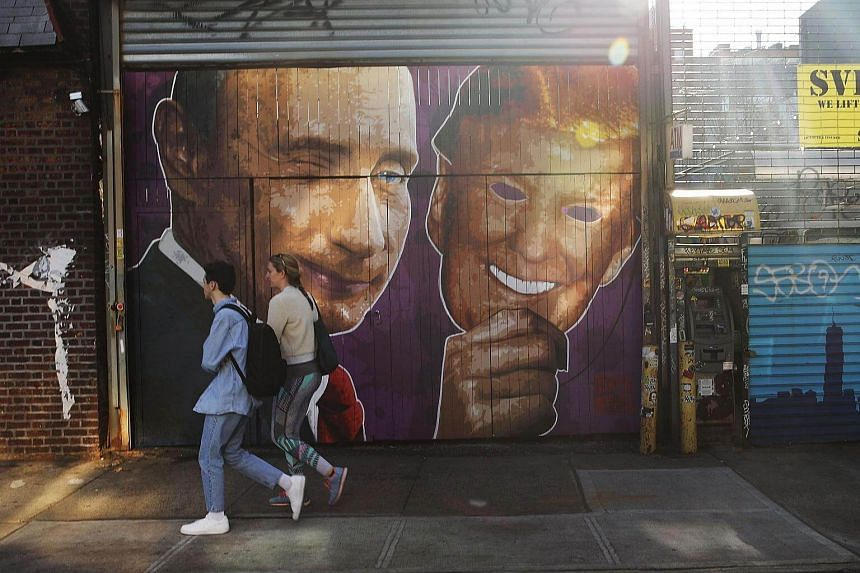 A mural depicting a winking Vladimir Putin taking off his Donald Trump mask is painted on a storefront outside of the Levee bar in Brooklyn.