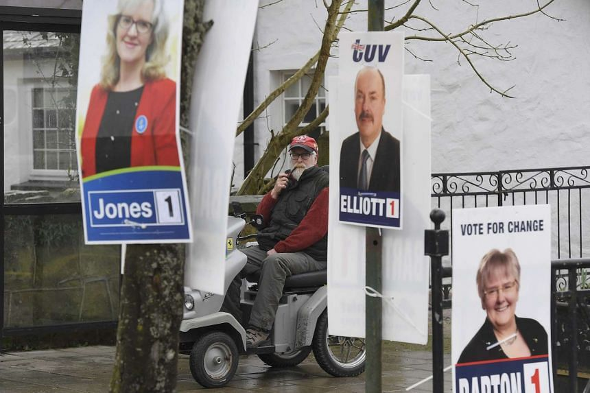 A man rides past campaign posters on polling day in Brookeborough, Northern Ireland, on March 2, 2017.