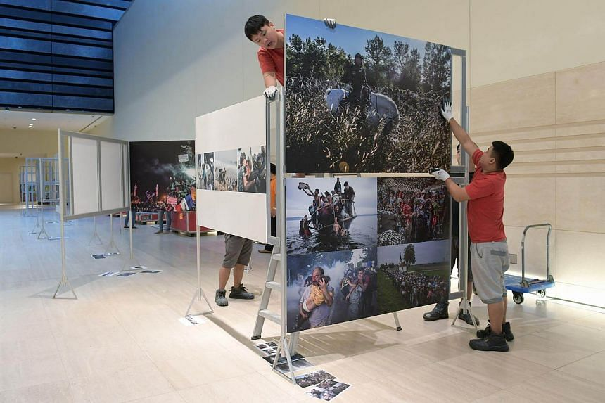 Workers from Sun Paradise setting up the World Press Photo 2016 exhibition at the National Museum of Singapore.