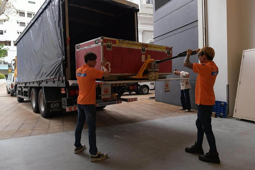 Workers from Sun Paradise, World Press Photo's logistics partner, moving crates containing the winning entries and other exhibition paraphernalia at the National Museum of Singapore.