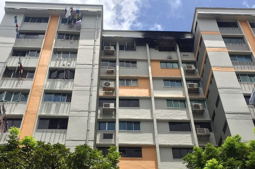 The 12th-floor unit at Block 220, Serangoon Avenue 4, that caught fire, with the exterior of the balcony blackened from smoke.