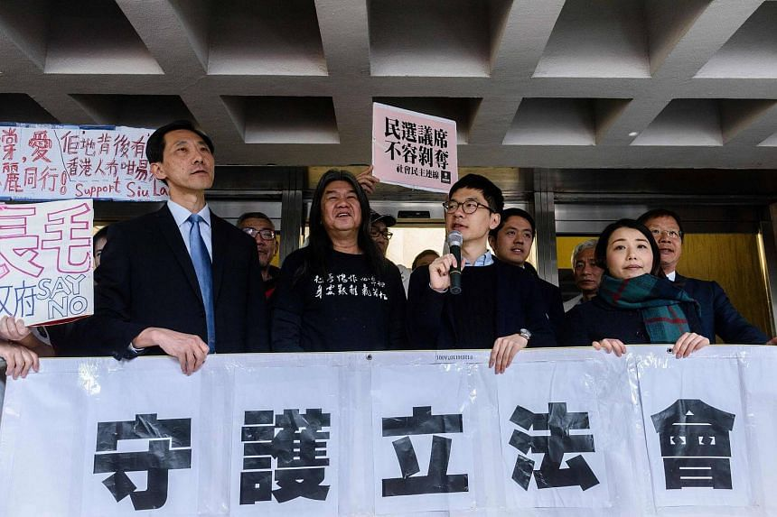 """Elected pro-democracy lawmakers (from left) Edward Yiu, """"Long Hair"""" Leung Kwok-hung, Nathan Law, and Lau Siu-lai hold a banner outside the High Court in Hong Kong on Mar 1, 2017."""