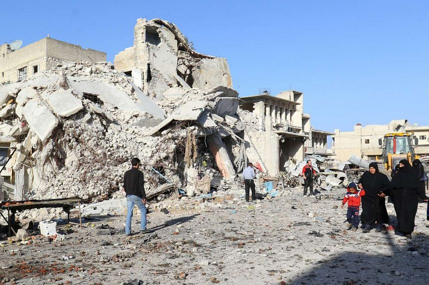 People walk at a site hit by airstrikes in the rebel-controlled town of Ariha in Idlib province, Syria, Feb 25, 2017.