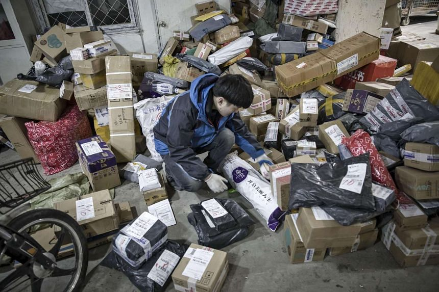 A courier sorts through packages at a ZTO Express Inc collection and distribution point in Shanghai, China.