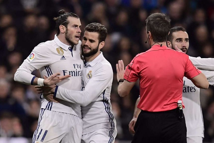 Bale (left) argues with the referee as Real Madrid's defender Nacho Fernandez (second left) tries to stop him.