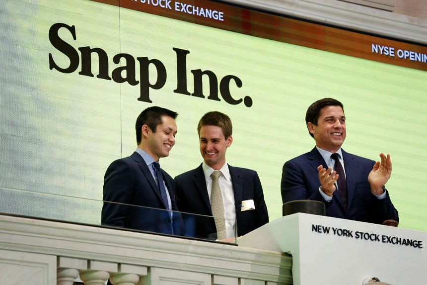 Snap cofounders Evan Spiegel (C) and Bobby Murphy ring the opening bell of the New York Stock Exchange, March 2, 2017.