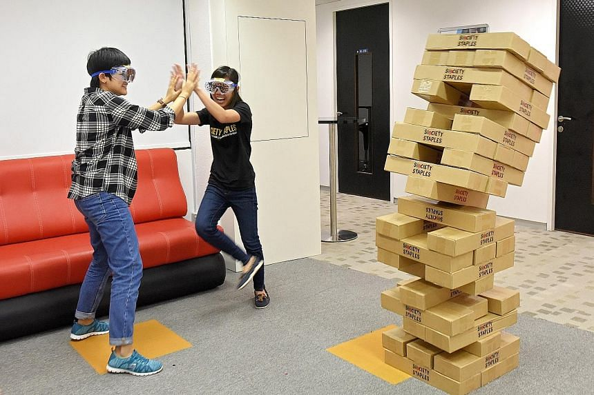 Events management executive Tay Puay Shan (left) and co-founder of Society Staples Debra Lam playing Giant Jenga with special goggles that simulate different kinds of visual disabilities.