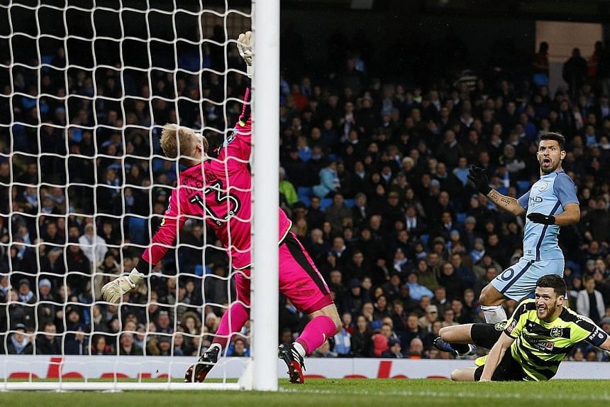 Sergio Aguero drilling past Huddersfield goalkeeper Joel Coleman to score Manchester City's fourth goal in the 73rd minute, taking his season tally to 22 goals in all competitions. Left: City goalkeeper Claudio Bravo gesturing to Huddersfield fans af