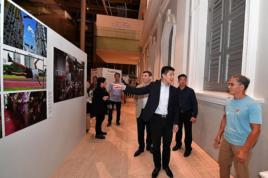 """Mr Tan Chuan-Jin chatting with retiree Ngai Hin Kwok (right), whose impressive """"human flag"""" move was captured by ST photojournalist Ng Sor Luan for a feature on active ageing. With them is ST editor Warren Fernandez. Visitors at the launch of the 201"""