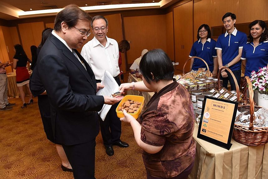 OCBC group chief executive Samuel Tsien getting a cookie at a booth set up by the Movement for the Intellectually Disabled of Singapore (Minds) at the launch of the bank's expanded CSR programme yesterday, as Minds CEO Keh Eng Song looks on.