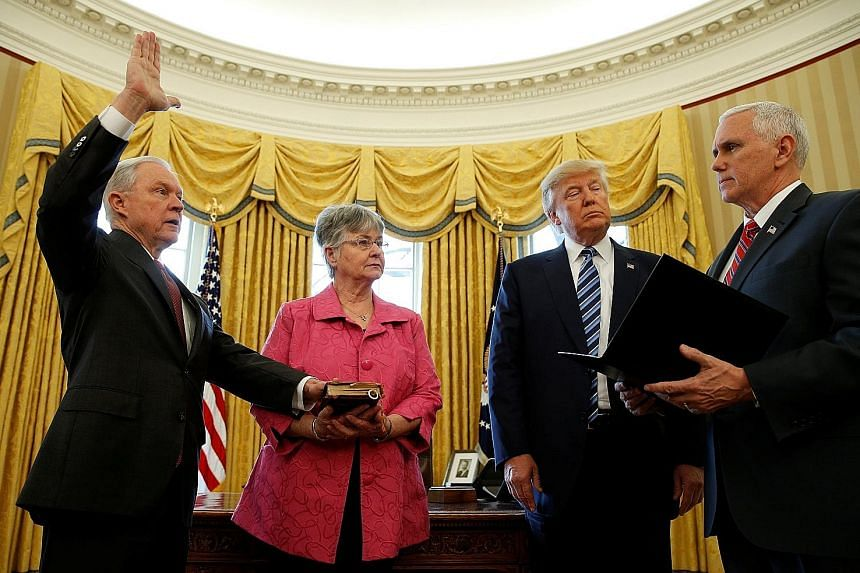 Mr Sessions being sworn in on Feb 9 by Vice-President Mike Pence, with Mrs Mary Sessions holding the Bible and President Trump looking on.