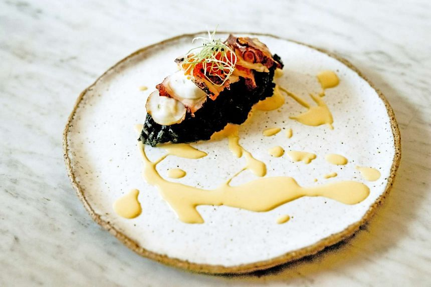Octopus on squid ink risotto with salted egg sauce and tobiko.