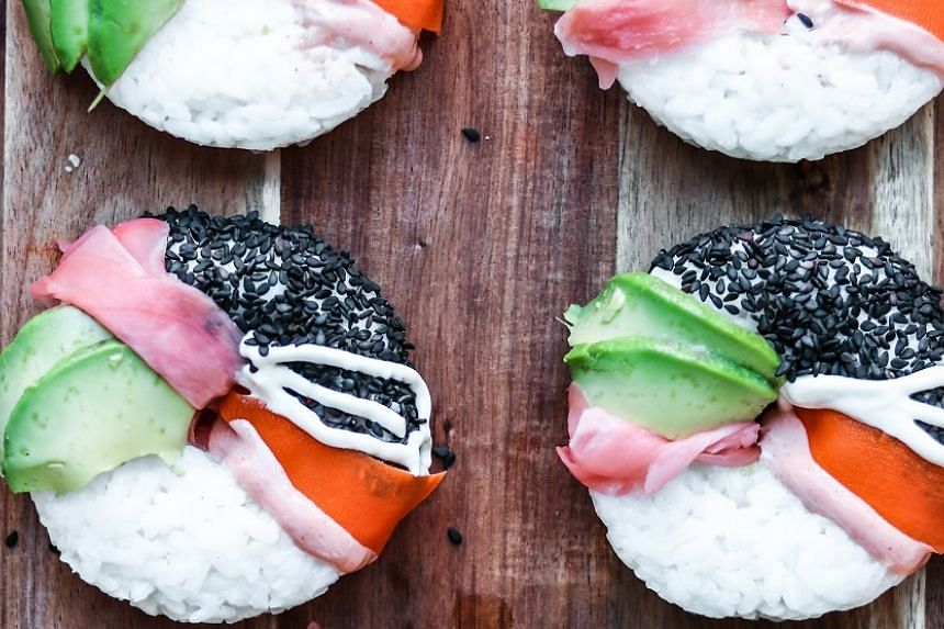Sushi doughnuts with avocado, sesame seeds, pickled ginger and carrot.