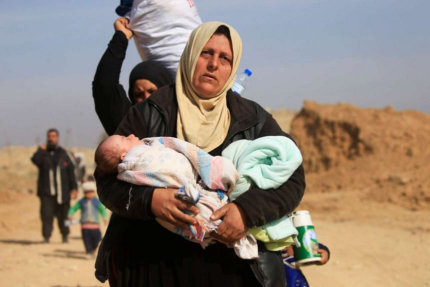 Displaced Iraqi people flee their homes, during the battle against the Islamic State of Iraq and Syria militants, at the district of al-Mamoun in Mosul, Iraq, on March 1, 2017.