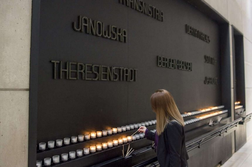 A woman lights a Memorial Candle during an International Holocaust Remembrance Day Commemoration at the United States Holocaust Memorial Museum in Washington, DC, on Jan 27, 2017.