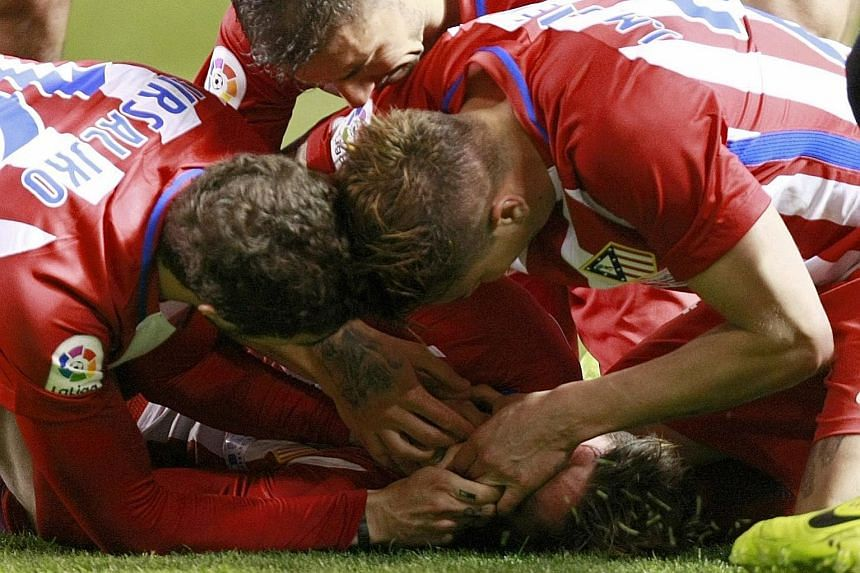 Deportivo players (from left) Sime Vrsaljko, Gabi and Jose Maria Jimenez trying to prevent Atletico striker Fernando Torres from swallowing his tongue after a clash of heads at the Riazor stadium in La Coruna. (Below) Torres getting medical assistanc