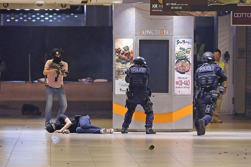 """A """"terrorist"""" in a shoot-out with police during a counter-terror exercise in Bishan's Junction 8 mall last October. New large-scale commercial buildings will be required to undergo a review at the design stage to determine what security measures are"""