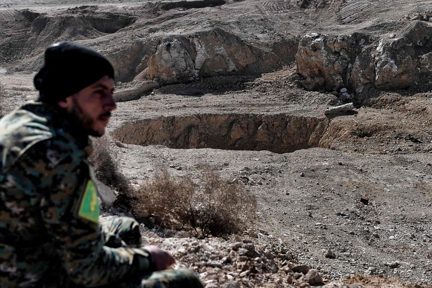 A paramilitary member by the infamous sinkhole, in the village of Athbah near Mosul. The scale of ISIS' atrocities at the site came to light only when the area was recaptured by Iraqi forces recently.