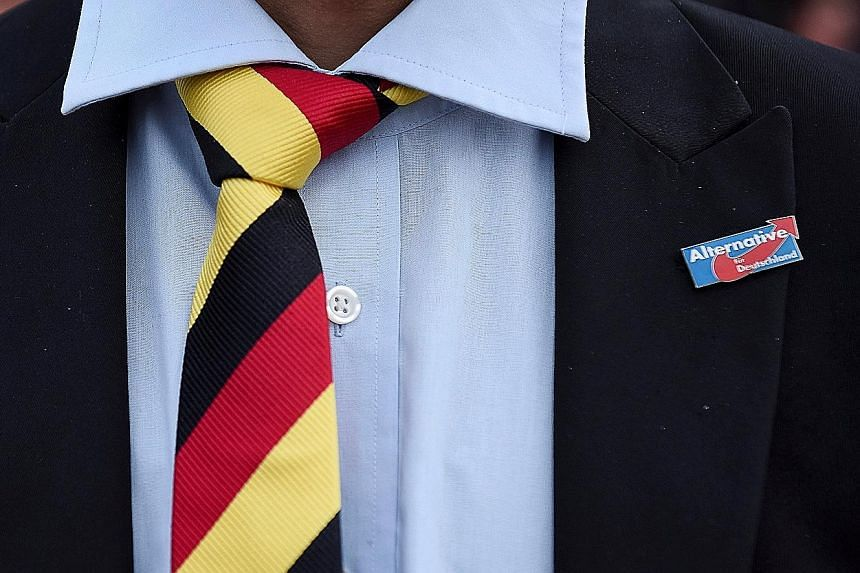 A man with a tie in Germany's national colours wearing a pin supporting the Alternative for Germany party. Recent polls show that support for the party has fallen significantly from a high of 15.5 per cent in December.