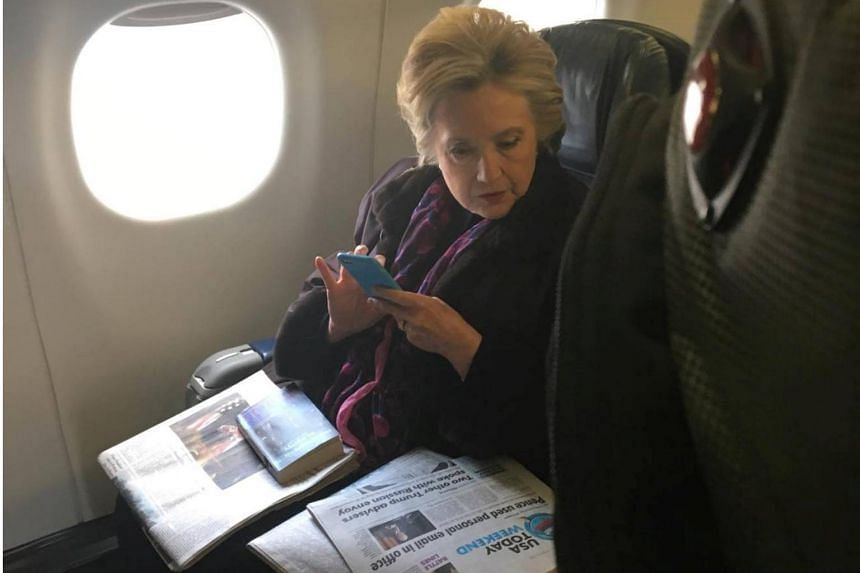 Former Democratic presidential candidate Hillary Clinton looks at a USA Today newspaper carrying an article about US Vice-President Mike Pence's use of personal e-mail while in office.