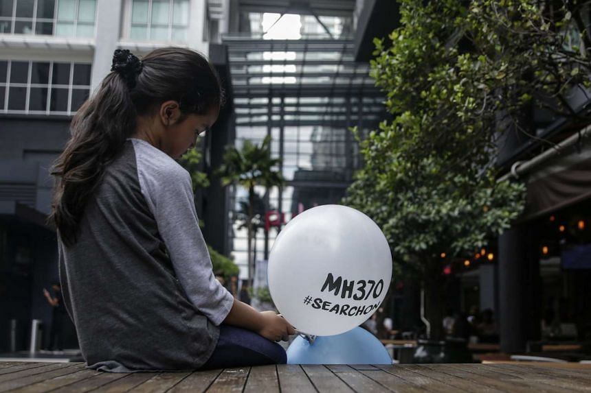 A relative of one of the victims holds a balloon with a 'MH370 #Searchon' message on it during a remembrance ceremony to mark the third anniversary of MH370's disappearance.
