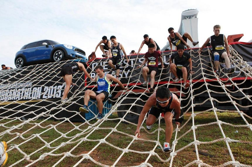 Participants of the Men's Health Urbanathlon challenge tackling one of the nine urban obstacles during the 2013 race.
