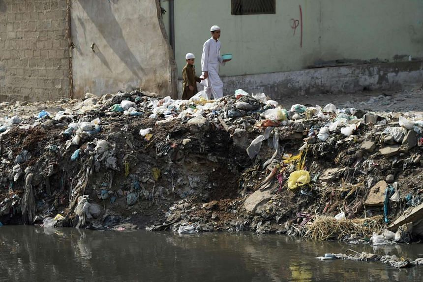 Pakistani youths walking past dumped garbage at a residential area of Karachi on Jan 24, 2017.