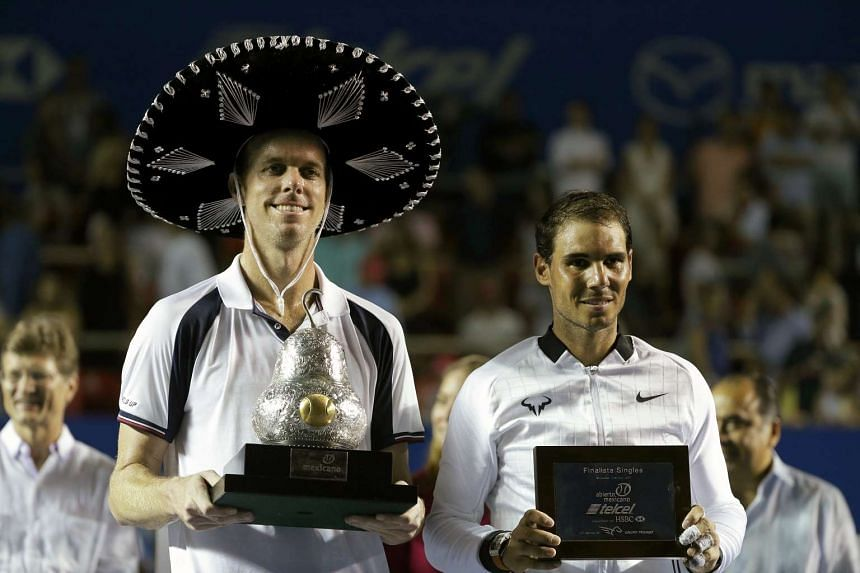 Sam Querrey (left) poses with the trophy after winning against Rafael Nadal in their Men's final match at the Mexican Open tennis tournament in Acapulco on March 4, 2017.