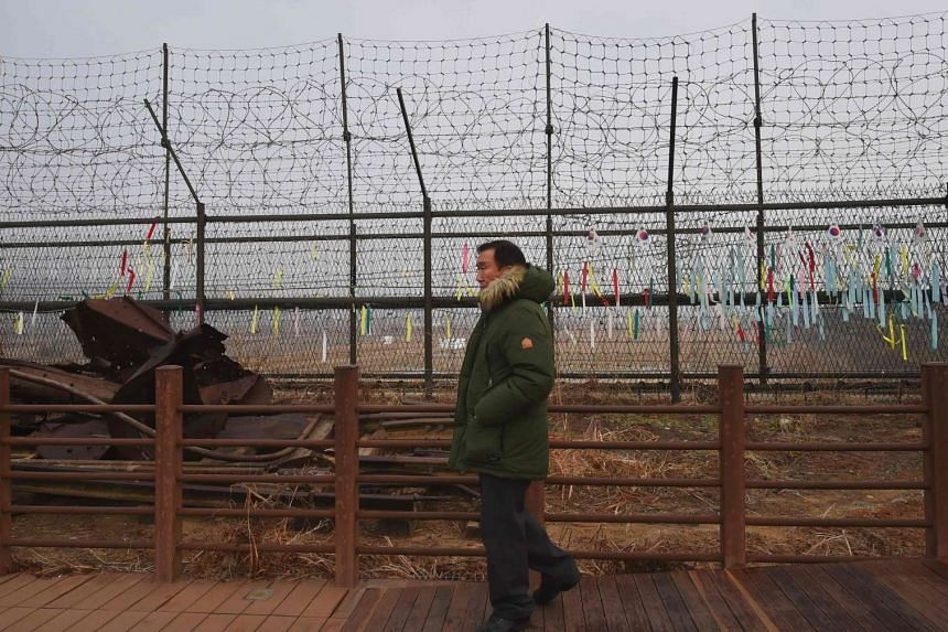 A man walks past a military barbed wire fence at the Imjingak peace park in the border city of Paju near the Demilitarized Zone dividing the two Koreas on Jan 1, 2017.