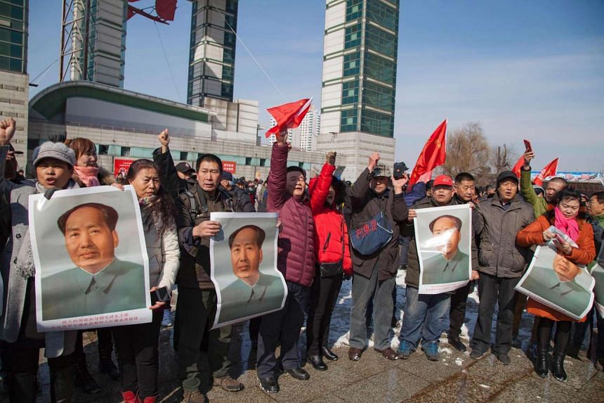 Demonstrators holding portraits of the late communist leader Mao Zedong staging a protest to boycott South Korean company Lotte, in Jilin, China, on March 5, 2017.