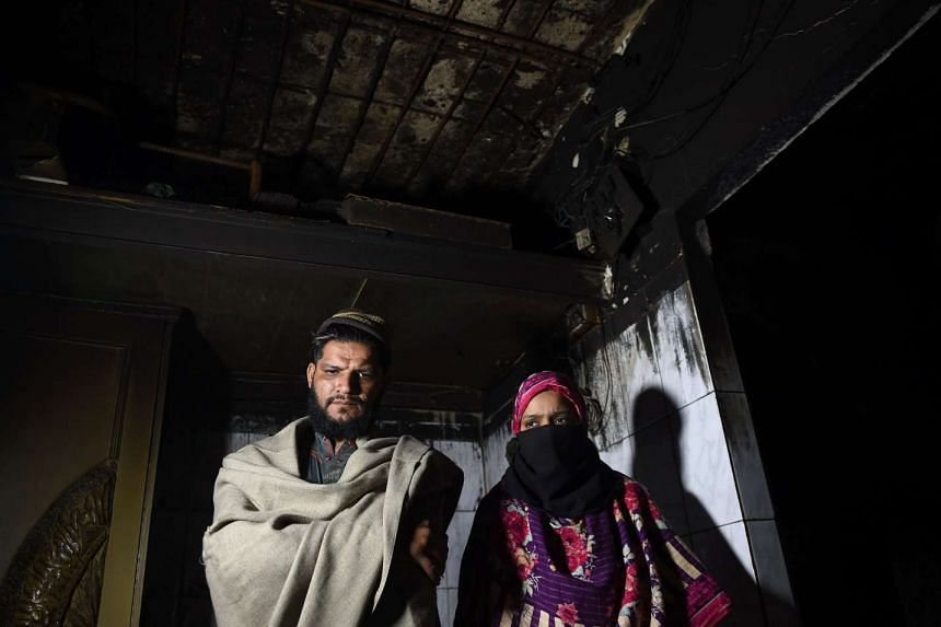 Mr Mohammad Umair and his wife Shameen standing inside the burnt-out bedroom in their apartment in Karachi, where three of their children were killed in a fire.