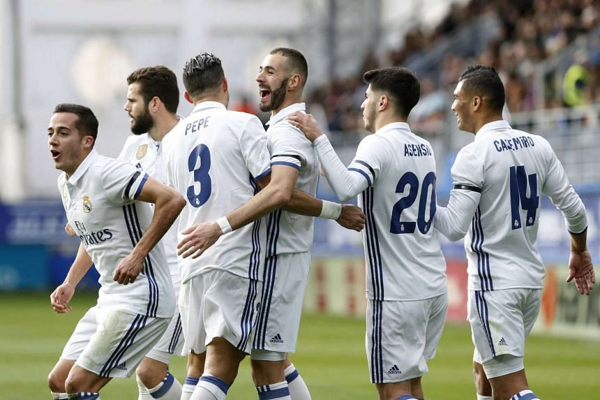 Real Madrid's French striker Karim Benzema (C) celebrates with teammates after scoring his second goal against Eibar.