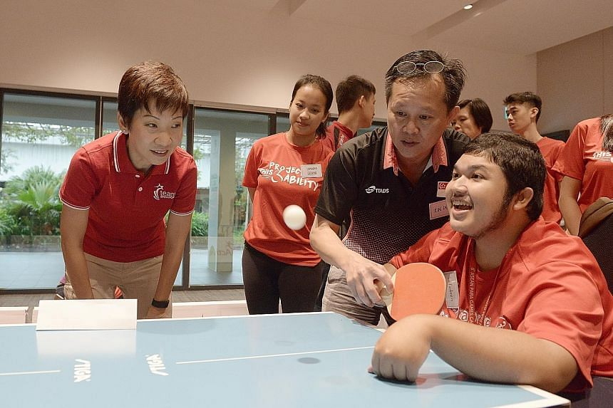 Minister for Culture, Community and Youth Grace Fu cheering Mr Muhd Saifudeen on as he took part in para table tennis at the event yesterday.