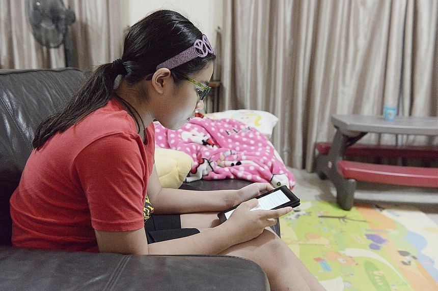 Ten-year-old Emily Selva reading an e-book on her Kindle in the living room of her Woodlands home. She and her younger sister, Calista, eight, get fewer than eight hours of sleep a night due to their busy schedules on school days.