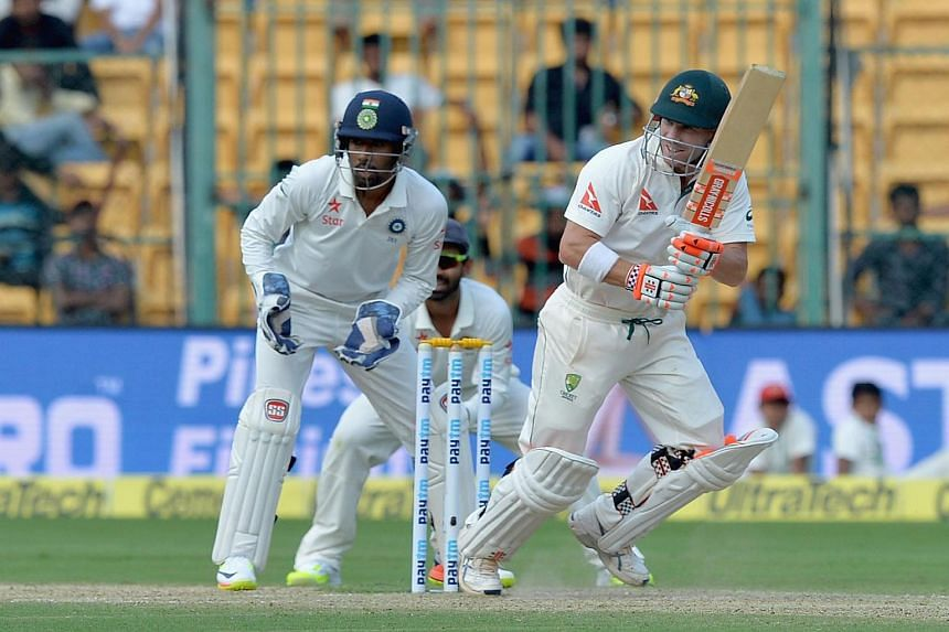 Australian batsman David Warner (right) is watched by India's wicket keeper Wriddhiman Saha as he plays a shot during the first day of the second cricket Test match between India and Australia on March 4, 2017.