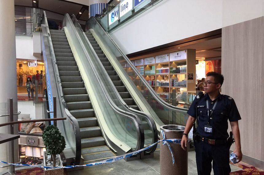 A police cordon is seen around an escalator on the third floor of Chinatown Point, after fire broke out in the shopping mall on March 5, 2017.