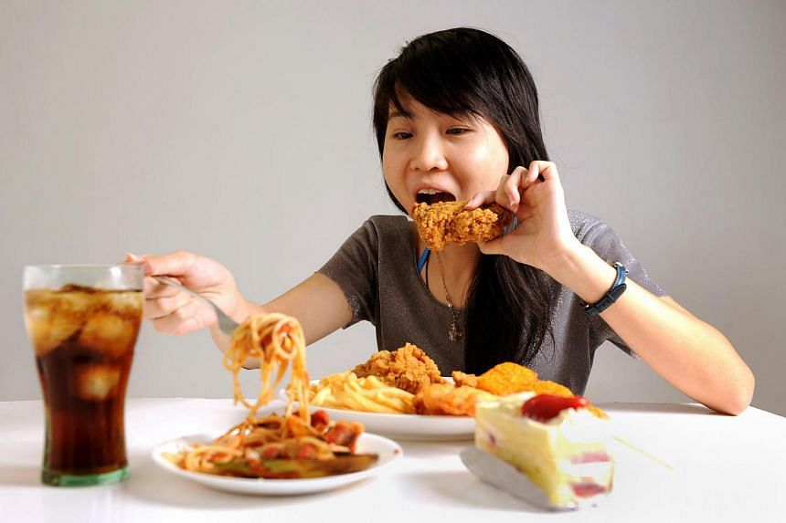 Posed photo of a teenager eating fried food.