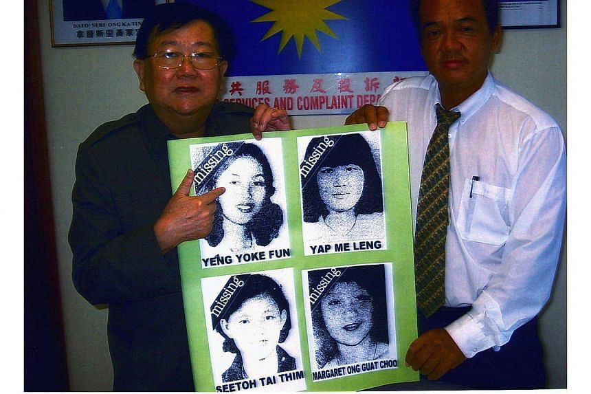 Datuk Michael Chong and James Hue displaying the pictures of four Malaysian women who were abducted in 1978, reportedly by North Korea agents, in 2005.