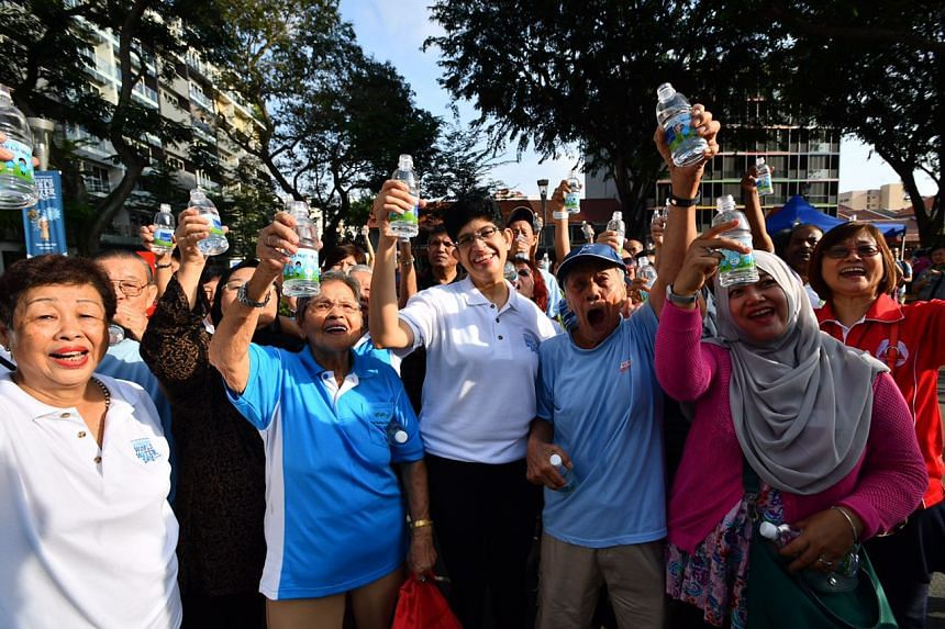 Associate Professor Fatimah Lateef (centre, in white) and Geylang Serai residents celebrating Singapore World Water Day at the Geylang River on March 5, 2017.
