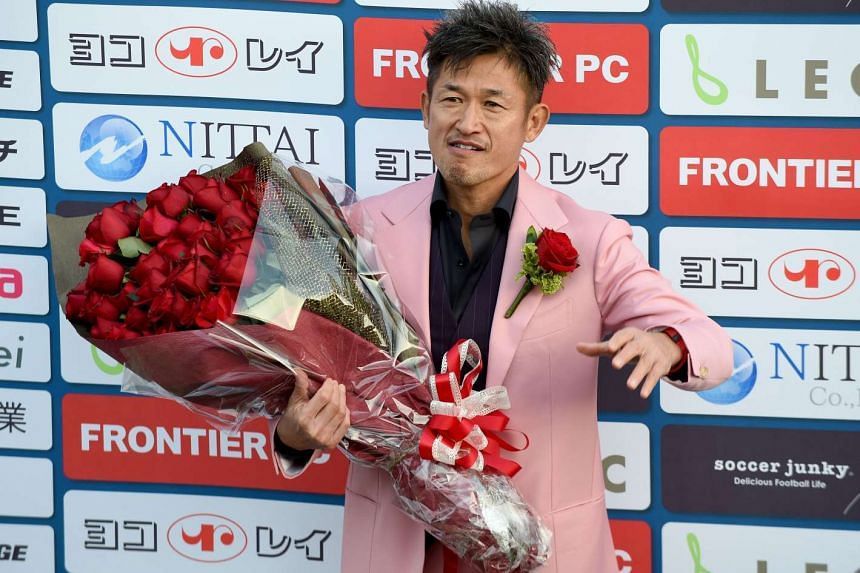 Kazuyoshi Miura posing with a bouquet of flowers presented to him by journalists to celebrate his 50th birthday, on Feb 26, 2017.
