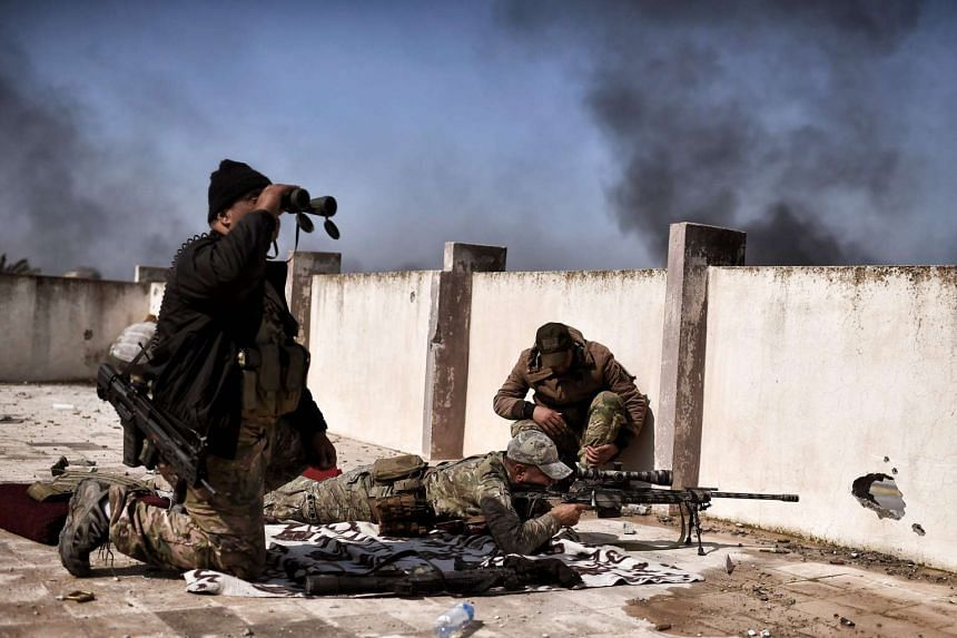 A sniper fires at targets during clashes with ISIS fighters in Mosul on March 5, 2017, during an offensive to retake the western parts of the city from the jihadists.