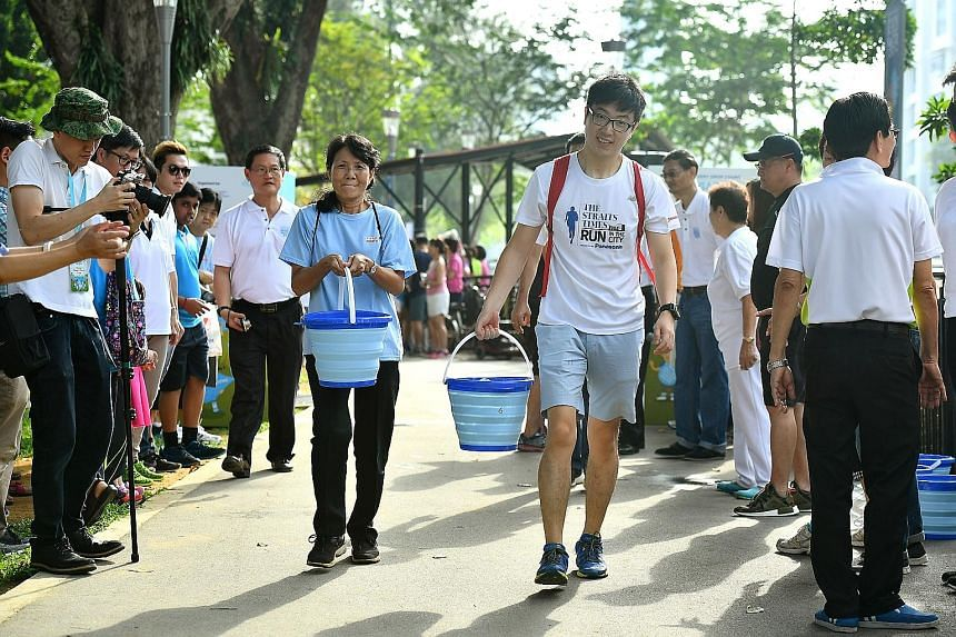 """Housewife Seah Wah Kiang, 59, and finance associate Yu Yang, 30, carrying recycled water in the """"Race for Water"""", one of the activities at an event yesterday to celebrate Singapore World Water Day. It was held next to the Geylang River."""
