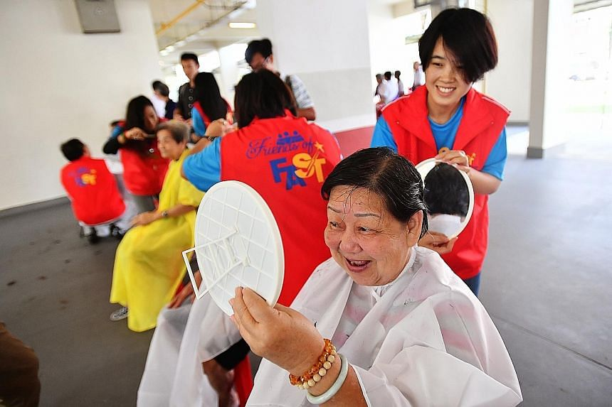 Madam Tay Noi Moi, 73, checking her hair after having it cut by Ms Yee Naung Htwe, 31, a student hairdresser from Myanmar. About 150 volunteers were at yesterday's community event in Ang Mo Kio, giving haircuts and manicures to underprivileged senior